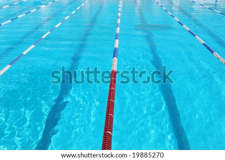 Lanes of sport swimming pool with turquoise water. Swimming pool with a lot od space for text. Swimmingpool lane markers. Swimming pool of olimpic type is ready for competition. Swimming pool surface. - stock photo