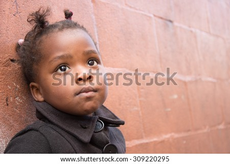 LANGA TOWNSHIP, SOUTH AFRICA - JULY 12, 2015 - A young girl poses for a photograph against a wall along a roadway in Langa, South Africa, a township located on the outskirts of Cape Town. - stock photo