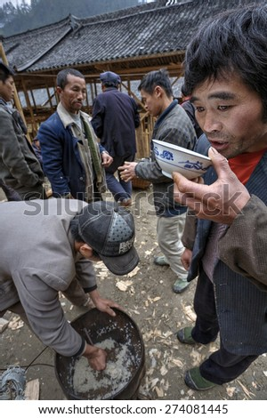Langde Village, Guizhou, China - April 16, 2010: Asian man drinking from a cup at the village celebration.
