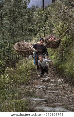 Langde Village, Guizhou, China - April 15, 2010: Chinese peasant farmer man carries the weight on your shoulder. Asian family farmer goes to work in  fields in highlands, boy runs next to his father. - stock photo