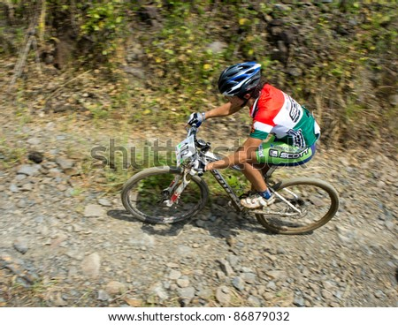 LANGKAWI, MALAYSIA - OCTOBER 18: An unidentified athlete participates in the Langkawi International Mountain Bike Challenge on October 18, 2011 in Langkawi, Malaysia. It is a 5-day stage race, from Oct. 18-22, 2011. - stock photo