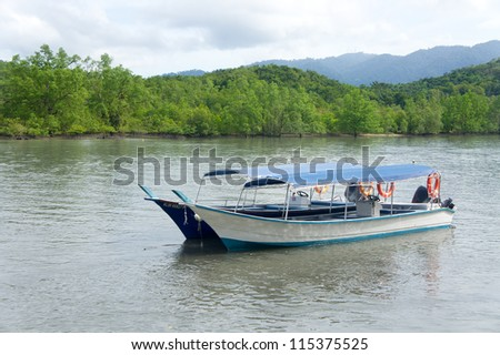 LANGKAWI- SEPT 29: Tourist boats at pregnant maiden island on September 29, 2011 in Langkawi, Malaysia. The pregnant maiden island is known to be the second largest island of the Langkawi archipelago - stock photo