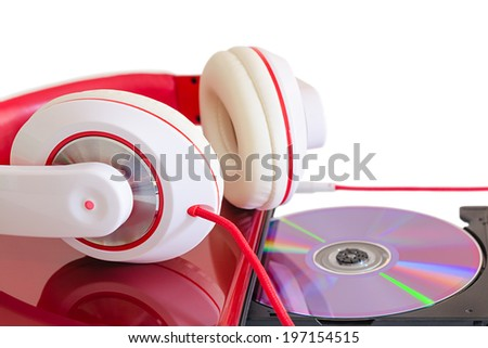 Language course learning with DVD compact disc in laptop and white red headphones on glossy notebook surface - stock photo
