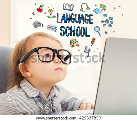Language school concept with toddler girl using her laptop - stock photo