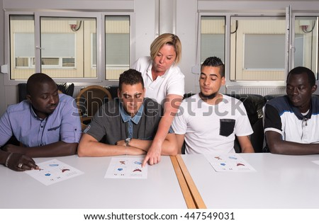 Language training for refugees in a German camp: A female German volunteer is teaching young African (Gambia) and Arabic (Algeria and Tunesia) men the German language in a refugee camp quickly - stock photo