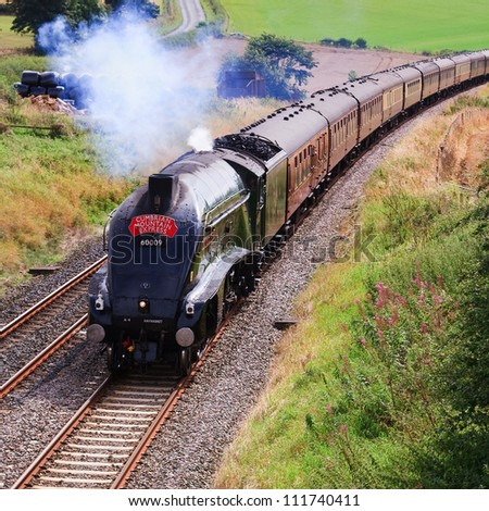 LANGWATHBY, ENGLAND - SEPTEMBER 1: Preserved Sir Nigel Gresley steam locomotive Union of South Africa is pictured south of Langwathby, England on September 1, 2012, on the Settle to Carlisle railway. - stock photo