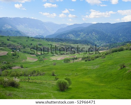 Lanscape of green field with some clouds on the sky - stock photo