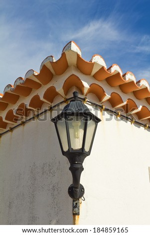 Lantern against the wall and roof under the blue sky - stock photo