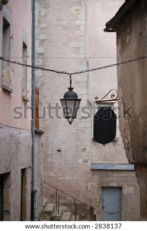 lantern hanging across an alley with a blank black sign