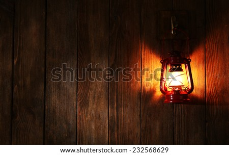 Lantern hanging on hook on wooden wall - stock photo