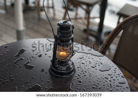 lantern on a wet cafe table after rain - stock photo