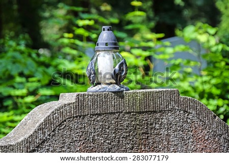 Lantern on the tombstone in the cemetery - stock photo
