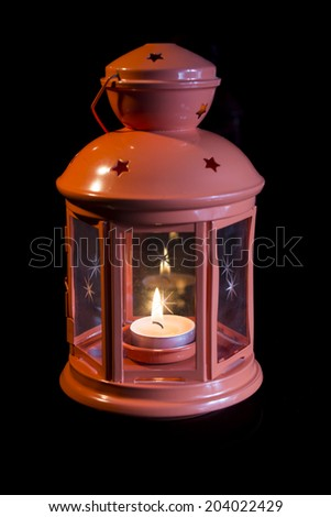 Lantern with a candle in it on blackground