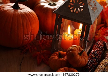 Lantern with burning candles and pumpkins - stock photo