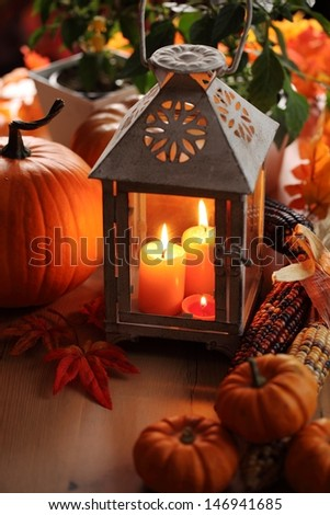 Lantern with candles, pumpkins and autumn decorations. - stock photo