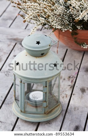 Lantern with heather on a wooden table - stock photo