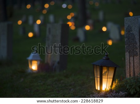Lantern with lit candle on grave at night - stock photo