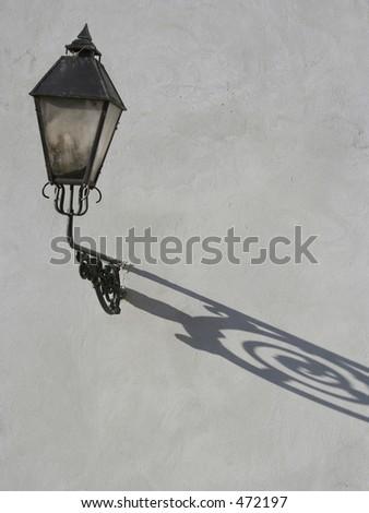 lantern with shadow on concrete wall - stock photo