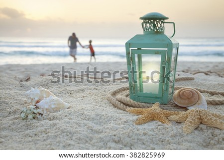 Lantern with shells on beach with soft focus father and son collecting shells in the background at sunrise