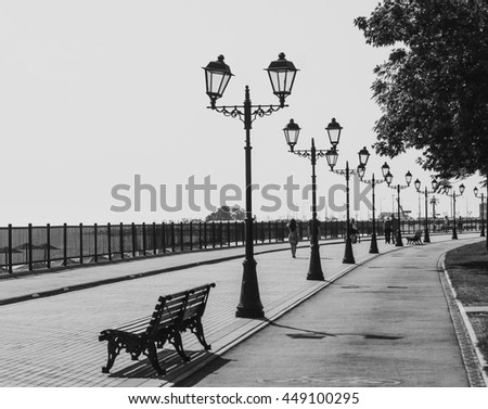 Lanterns and benches on the waterfront - stock photo