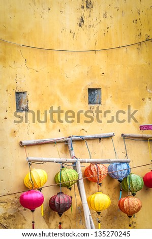 Lanterns of different colors hanging from sticks in Hoi An. Traditional asian lamps made of paper. Yellow wall of old building with two small windows. Equipment for cultural events in Vietnam, Asia. - stock photo