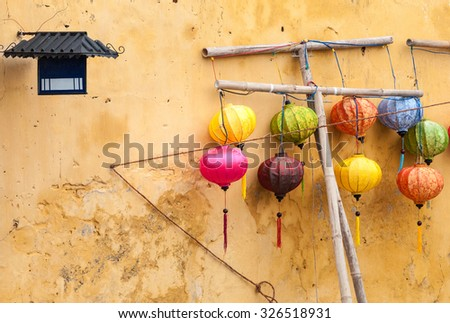 Lanterns of different colors hanging from sticks in Hoi An. Traditional asian lamps made of paper. Yellow wall of old building with two small windows. Equipment for cultural events in Vietnam, Asia.