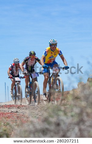 "LANZAROTE, SPAIN - MAY 03: Oscar de Leon N69, Leon Martin N83,Andres Serrano N206 in action at Adventure mountain bike marathon ""Ultrabike Santa Rosa"" May 03, 2015. Lanzarote, Canaries islands, Spain. - stock photo"