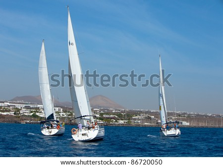 LANZAROTE, SPAIN - OCT. 11: three fully crewed yachts  with numbers  5, 3 and 4 out sailing with white sails   in the  Russian BOSS Regatta, Oct.  11 2011, Canary islands, Spain - stock photo