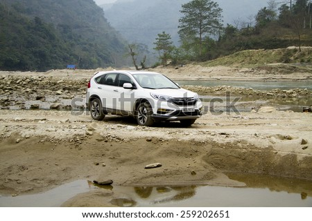 Lao Cai, Viet Nam - Feb 10, 2015: An SUV Honda model CRV 2015 runing on the bad road in Vietnam - stock photo