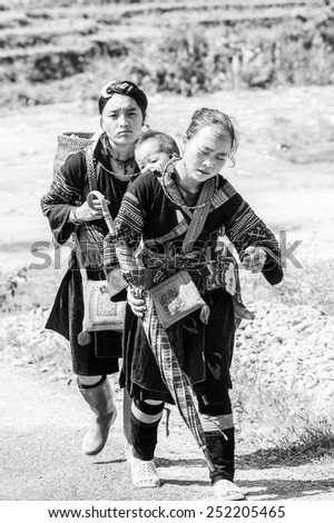 LAO CHAI VILLAGE, VIETNAM - SEP 22, 2014: Unidentified Hmong woman carries her little baby on her back in Lao Chai. Hmong is on of the minority eethnic group in Vietnam