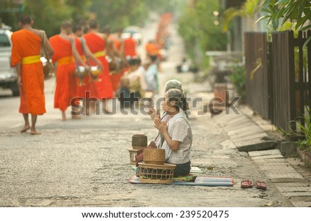 Lao People's Democratic Republic, Laos, Luang Prabang - 20 JUNE: Woman prays after giving alms to buddhist monks on the street, Luang Prabang, 20 JUNE 2014. - stock photo