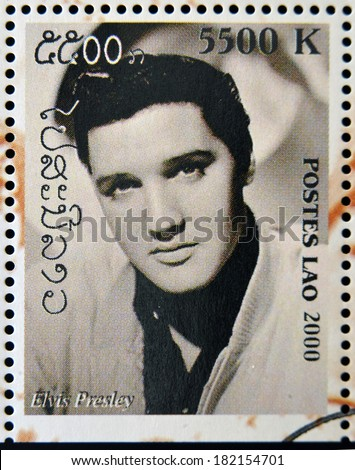 LAOS - CIRCA 2000: A stamp printed in Laos showing Elvis Presley, circa 2000  - stock photo
