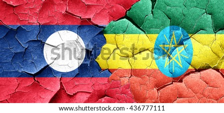 Laos flag with Ethiopia flag on a grunge cracked wall - stock photo