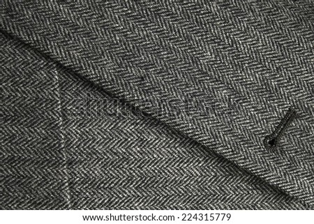 Lapel detail and front pocket of a classic gray woolen tweed coat - stock photo