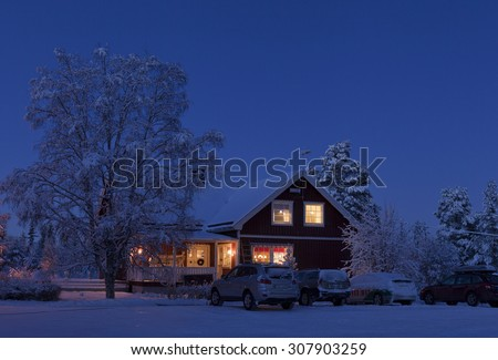 LAPLAND, SWEDEN ON DECEMBER 24. Winter house and vehicles in the night on December 24, 2014 in Lapland, Sweden.  Farm buildings after sunset up North on Christmas Eve, cars this side.