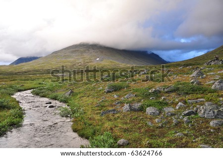 Lappland landscape along  Kungsleden hiking path with river and mountain - stock photo