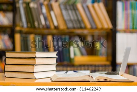 laptop and a stack of books in the library - stock photo