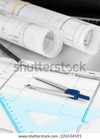 Laptop and blueprint rolls - stock photo