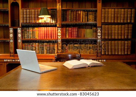 Laptop and book lying on a desk in classic library - stock photo