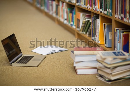 Laptop and books on the library floor in college - stock photo