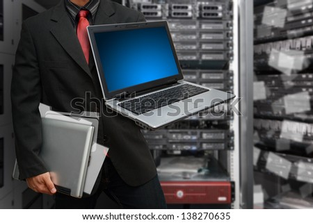 Laptop and business man in data center room