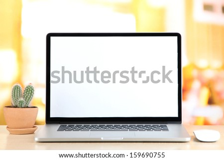 Laptop and cactus in flowerpot on wooden table - stock photo