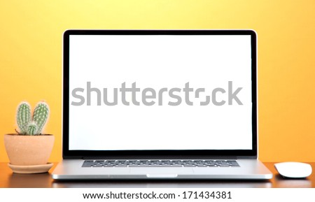 Laptop and cactus in flowerpot on wooden table on yellow background