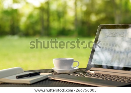 Laptop and coffee, outdoor office - stock photo