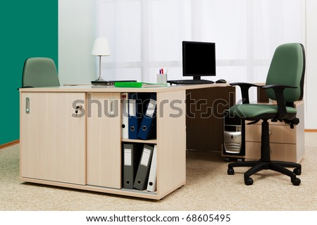 laptop and computer on a desk in a modern office - stock photo