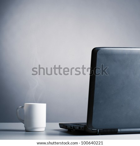 laptop and cup of hot evaporating coffee on table, blue toned - stock photo