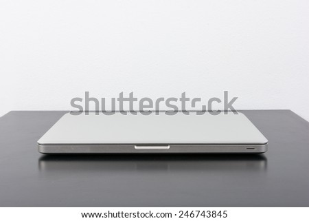 Laptop and flower pot on black wooden table on wall background - stock photo