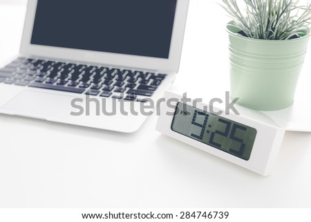Laptop and flower pot with clock