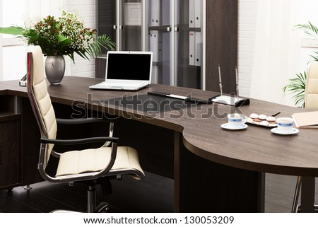 laptop and flowers on the table in a modern office