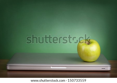 Laptop and green apple on a table - stock photo